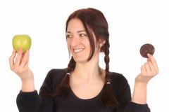 Donna che sceglie fra la mela ed i biscotti del cioccolato Fotografia Stock