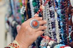Donna che sceglie gioielli nella fila delle collane e dei braccialetti Fotografia Stock