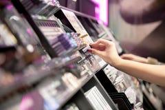 Donna che sceglie i cosmetici di colore nei cosmetici del deposito Fotografia Stock