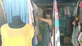 Donna che sceglie i vestiti al mercato video d archivio
