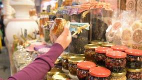 Donna che sceglie il barattolo del miele con differenti dadi archivi video