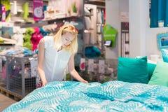 Donna che sceglie il giusto oggetto per il suo appartamento in un deposito moderno dell'arredamento domestico fotografia stock libera da diritti