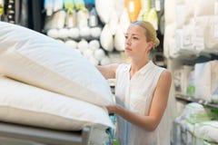 Donna che sceglie il giusto oggetto per il suo appartamento in un deposito moderno dell'arredamento domestico immagini stock