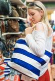 Donna che sceglie la borsa della spiaggia Immagini Stock