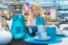 Donna che sceglie la decorazione giusta per il suo appartamento in un deposito moderno dell'arredamento domestico Immagine Stock