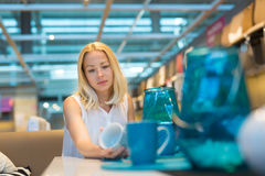 Donna che sceglie la decorazione giusta per il suo appartamento in un deposito moderno dell'arredamento domestico Fotografia Stock Libera da Diritti