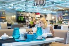 Donna che sceglie la decorazione giusta per il suo appartamento in un deposito moderno dell'arredamento domestico Fotografia Stock