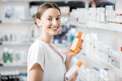 Donna che sceglie la lozione della protezione solare alla farmacia fotografia stock