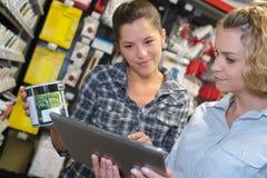 Donna che sceglie la pittura di colore durante l'acquisto dell'hardware nel miglioramento domestico immagini stock