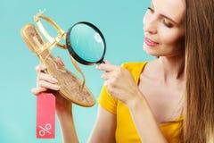 Donna che sceglie le scarpe che cercano tramite la lente d'ingrandimento Immagine Stock Libera da Diritti