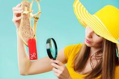 Donna che sceglie le scarpe che cercano tramite la lente d'ingrandimento Immagine Stock