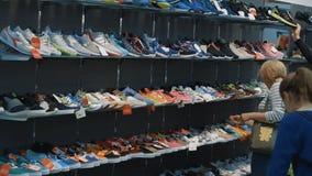 Donna che sceglie le scarpe in deposito archivi video