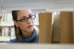 Donna che sceglie libro in libreria Fotografia Stock
