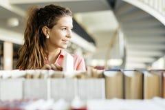 Donna che sceglie un libro dallo scaffale in una biblioteca Immagine Stock