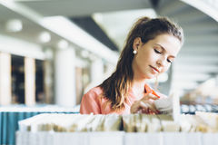 Donna che sceglie un libro dallo scaffale in una biblioteca Fotografie Stock Libere da Diritti