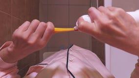 Donna che schiaccia dentifricio in pasta sullo spazzolino da denti al bagno video d archivio
