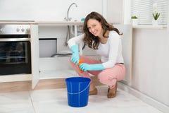 Donna che schiaccia panno bagnato nel secchio fotografia stock