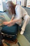 Donna che scorre veloce per chiudere con chiusura a lampo bagagli all'aeroporto Fotografia Stock Libera da Diritti