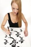 Donna che scrive calligrafia cinese: AMORE Fotografia Stock