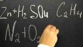 Donna che scrive formula di chimica sul bordo nero video d archivio