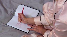 Donna che scrive parola di sforzo nel rosso sul taccuino stock footage