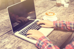 Donna che scrive su un computer portatile con una tazza di caffè Immagini Stock