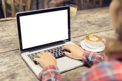 Donna che scrive su un computer portatile con una tazza di caffè Fotografia Stock Libera da Diritti