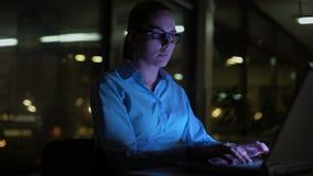 Donna che scrive sul computer portatile alla notte, overhours di lavoro in ufficio, stile di vita occupato archivi video