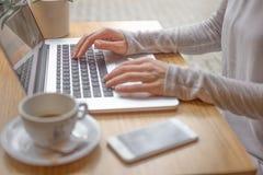 Donna che scrive sul computer portatile e che per mezzo dello Smart Phone Immagine Stock Libera da Diritti
