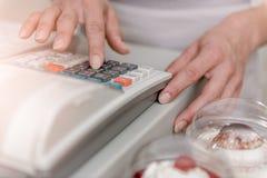 Donna che scrive sul registratore di cassa Immagini Stock