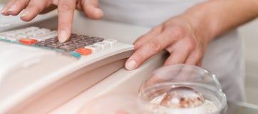 Donna che scrive sul registratore di cassa Fotografia Stock
