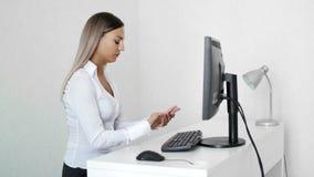 Donna che scrive sulla tastiera di computer che ha dolore del polso in ufficio Sindrome del tunnel carpale video d archivio