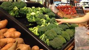 Donna che seleziona i broccoli freschi in drogheria video d archivio
