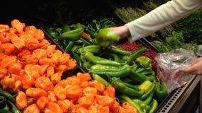 Donna che seleziona i peperoni verdi in drogheria video d archivio