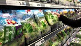Donna che seleziona il corredo dell'insalata di caesar del sussidio in drogheria archivi video