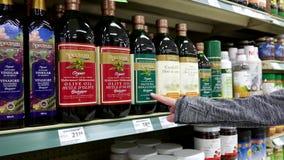Donna che seleziona l'olio d'oliva organico di spettro stock footage