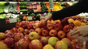 Donna che seleziona le mele rosse fresche in drogheria archivi video