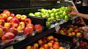 Donna che seleziona le mele verdi fresche in drogheria stock footage