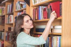 Donna che seleziona un libro da una biblioteca Immagine Stock Libera da Diritti