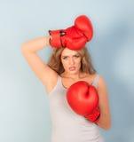 Donna che sembra i guantoni da pugile rossi d'uso stanchi Immagine Stock