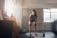 Donna che sembra messa a fuoco circa il suo allenamento di forma fisica Fotografia Stock