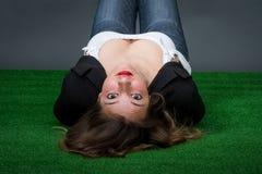 Donna che sembra trovantesi nell'erba fotografia stock