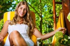 Donna che si abbronza al sole nel suo giardino Immagini Stock