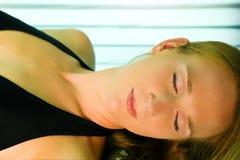 Donna che si abbronza nel solarium Immagine Stock
