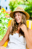 Donna che si abbronza nel suo giardino sulla sedia di salotto Immagine Stock