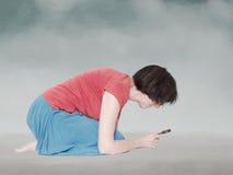 Donna che si accovaccia per studiare qualcosa sotto la lente d'ingrandimento Immagine Stock Libera da Diritti