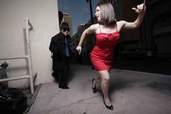Donna che si allontana dall'inseguitore Fotografia Stock