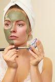 Donna che si applica con la maschera del fango dell'argilla della spazzola al suo fronte Fotografie Stock