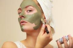 Donna che si applica con la maschera del fango dell'argilla della spazzola al suo fronte Fotografia Stock Libera da Diritti