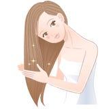 Donna che si applica olio per capelli ai suoi capelli lunghi Fotografia Stock